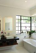Free-standing bathtub and black floating washstand in bathroom