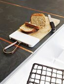 Bread and knife on chopping board on charcoal-grey kitchen worksurface