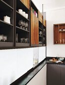 Crockery and glasses on elegant fitted shelves above serving hatch