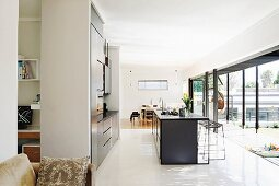 View past free-standing counter and fitted kitchen to summery terrace and dining area