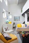 Wohnzimmerecke mit bunten Kissen auf Sitzmöbeln und Galerieebene