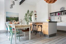 Kitchen counter with wooden fronts and dining table with thick wooden top in open-plan kitchen with eclectic ambiance