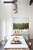 Rustikaler Esstisch mit weisser, aufgelegter Tischplatte vor Fotokunstbild und Vasensammlung