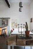 Esstisch mit rustikalen Holzbohlen und weisser, aufgelegter Platte in offener Küche