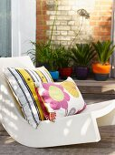 Colourful striped and floral cushions on white outdoor armchair
