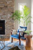 Reading corner with blue armchair in front of palm tree and brick fireplace