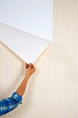 Peeling yellow-and-white striped wallpaper from wall