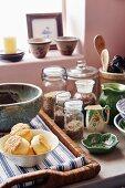 Storage jars, ceramic crockery and pastries on wicker tray