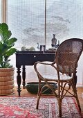 Antique desk and cane chair in front of bamboo roller blind
