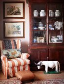 Porcelain vases in display cabinet next to loose-covered armchair and footstool