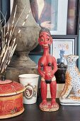 Red ethnic sculpture of woman next to animal figurine and beaker printed with Queen Elizabeth II motif