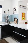 Black fitted kitchen units with white worksurface and splashback of pale blue wall tiles