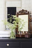 Antique vanity mirror, perfume bottles and glass vase of cow parsley on top of black bathroom cabinet
