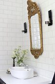 White countertop sink below gilt-framed mirror in vintage-style bathroom