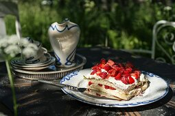 Strawberry cake and crockery on garden table