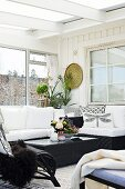 Black wicker coffee table and comfortable couch in conservatory extension with Scandinavian ambiance