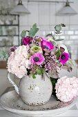 Romantic spring arrangement of hydrangeas, anemones and lilac