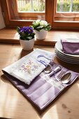 Silver cutlery in embroidered cutlery pouch next to stacked plates and potted primulas