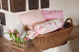 Hand-made bolster and pink cushions in wicker basket next to tulips on rustic stove bench