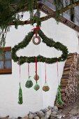 Mit Tannenzweigen umwickelter Drahtbügel mit aufgehängten DIY-Futterknödeln