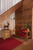Festive arrangement on wooden shelves against rustic wooden wall below staircase in hallway