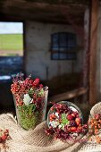 Rose hips, blackberries, heather and moss in glass jars