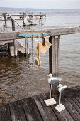 Bunch of keys, back scrubber and necklace hanging from key hanger hand-made from driftwood attached to jetty railing