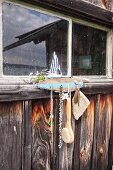 Key hanger hand-made from driftwood attached to boat house and decorated with model sailing boat