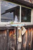 DIY-Schlüsselbrett aus Treibholz an Bootshaus mit Modellsegelboot dekoriert