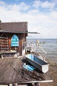 Zink-Badewanne auf Holzterrasse vor Bootshaus mit DIY-Gegenständen in Blautönen
