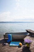 Zinc bathtub with wooden bath mat made from painted wooden laths on seaside jetty