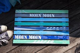 Wooden bath mat made from wooden laths painted in shades of blue