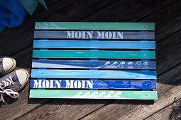 DIY-Fussmatte aus lackierten Holzleisten in Blautönen