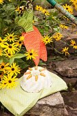 Carrot bundt cake on green cushion and hand-made carrot-shaped potholders in garden