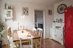 Rustic dining table, various chairs, white bureau and red fridge-freezer in dining area