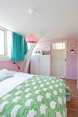 Pink wallpaper and turquoise curtains in attic bedroom