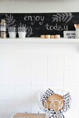 Bread basket in front of white wall tiles below kitchen shelf with chalkboard back wall