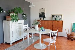 Round table and high chair in dining area with white vintage cabinet and retro sideboard