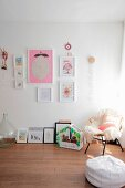 Pale sheepskin and pink cushion on wicker chair next to various child's drawings and cacti in small house