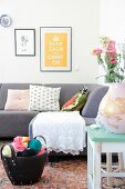 White crocheted blanket and various cushions on grey sofa below black-framed pictures