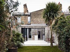 Traditional brick house with extension seen from garden with yucca palm tree