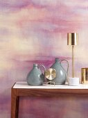 Retro vases and brass table lamp against wall marbled in pink and purple