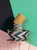 Woven baskets with zigzag patterns against wall with geometric pattern of bright colours