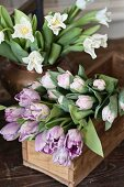 Tulips of various colours in wooden crate and vase