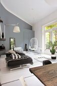 Couch, hanging chair, wall lamp and plants in modern living room in shades of grey with rustic wooden table in foreground