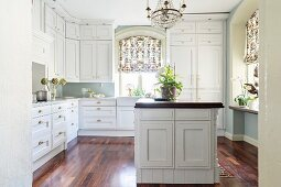White fitted kitchen with ceiling-high wall-mounted cupboards and island counter