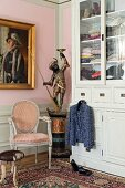 Antique statue, gilt-framed painting and wardrobe in corner of bedroom