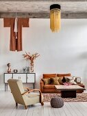 Retro furniture, concrete ceiling and ethnic clothing hung on wall above sideboard in living area