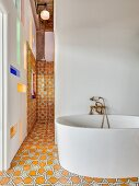 Free-standing modern bathtub against white wall in front of shower area with ornate floor and wall tiles