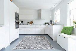 Elegante, weisse Einbauküche mit Sitztruhe unter dem Fenster, Teppich mit grafischem Muster